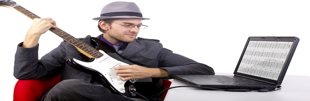 Man playing his guitar following the notes form his laptop